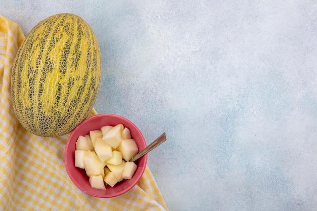 白い表面に黄色のチェックのテーブルクロスにピンクのボウルにスライスとメロンのトップビュー