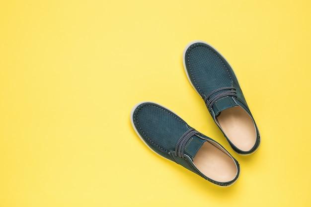 노란색 배경에 남자 여름 천공 신발의 상위 뷰. 편안한 여름 남성 신발.