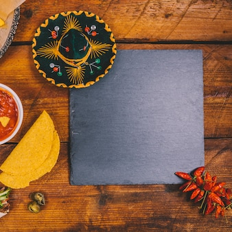 Top view of mexican hat; salsa sauce; tortilla; black slate and red chilies over wooden bench