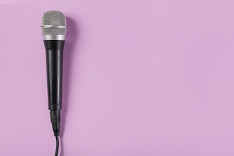 Top view of microphone on pink background