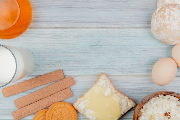 Вид сверху молочных продуктов в виде молочного творога, намазанного на ломтик хлеба с печеньем сливочного масла, пряники, яйца на деревянном столе с копией пространства