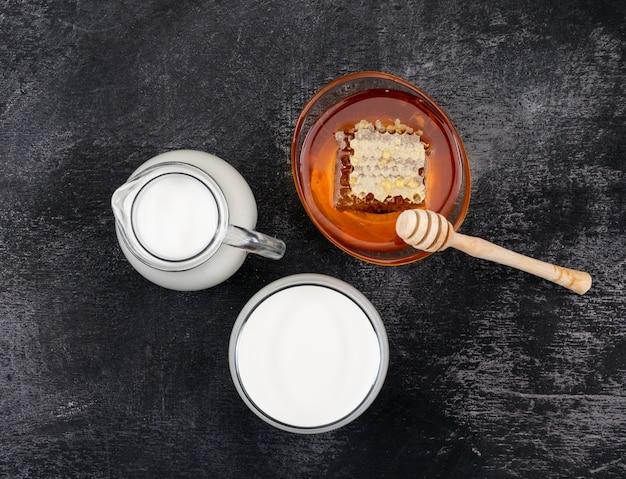 Вид сверху молока с медом на черной горизонтальной поверхности