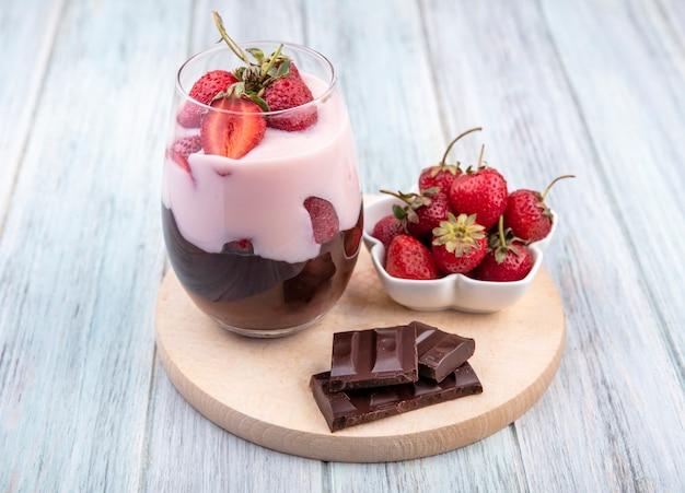 Вид сверху молочного коктейля с клубникой и шоколадом на деревянной кухонной доске на серой поверхности