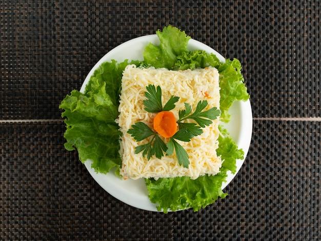 Вид сверху салат мимоза украшенный петрушкой и морковью