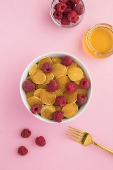 ピンクの表面の白いボウルにラズベリーとミニパンケーキの上面図