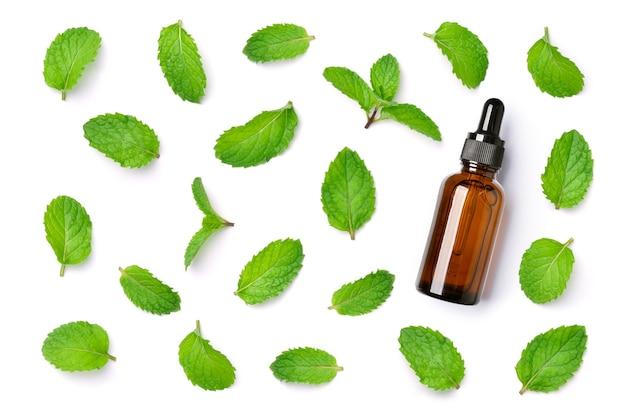 ミントの葉のパターンの上面図は、白い背景で隔離の琥珀色のスポイトボトルにエッセンシャルオイル。