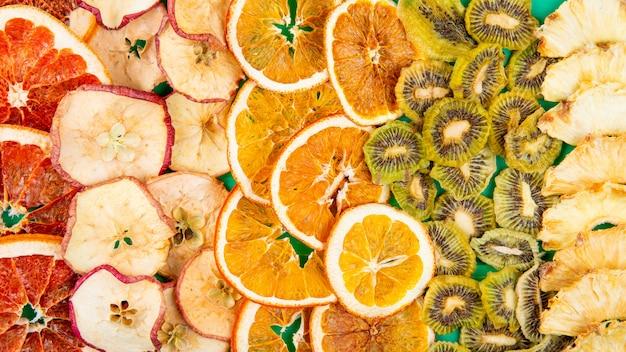Вид сверху смеси сухофруктов и кусочков цитрусовых яблок, апельсинового киви и ананасового фона из сухофруктов и цитрусовых