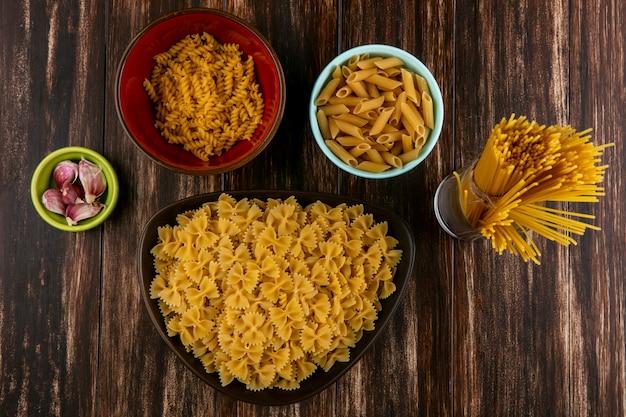 Вид сверху смеси сырых макарон в мисках с сырыми спагетти и чесноком на деревянной поверхности