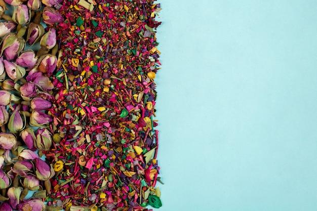 Вид сверху смешанного травяного чая цветет лепестками роз сушеные розы и травы на синем