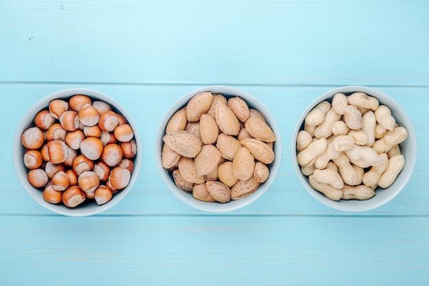 Вид сверху смешанных орехов фундука, миндаля и арахиса в скорлупе в мисках на синем фоне деревянных