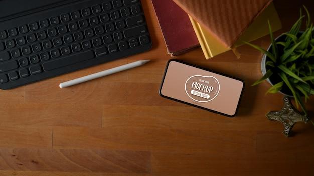 デジタルタブレット、ノートブック、コピースペースを備えた作業台の水平方向のスマートフォンの画面をモックアップする平面図