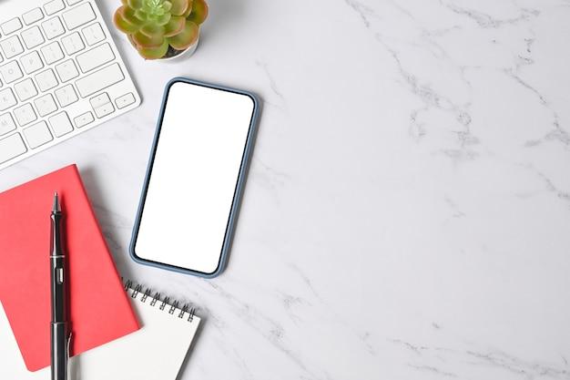 大理石の背景に空の画面、キーボード、ノートブックのモックアップ携帯電話の上面図。
