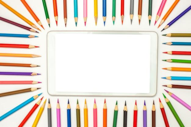 Вид сверху макета цифрового планшета на белом столе с рамкой разноцветных карандашей для рисования