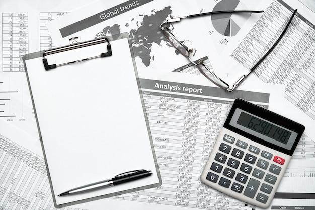 ノートブック、鉛筆、財務諸表などを備えたモダンな黒いオフィスデスクの上面図。フラットレイテーブルレイアウト。
