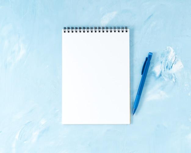 現代の明るい青いオフィスデスクトップペンまたは鉛筆、メモ帳の平面図。 、 空の