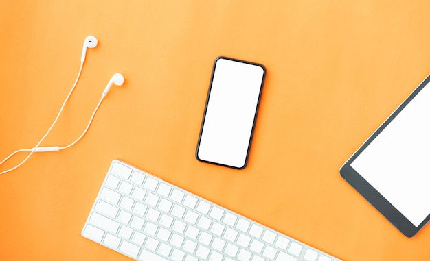 オレンジ色の背景に現代のスマートフォン、タブレット、白いヘッドフォンの平面図です。