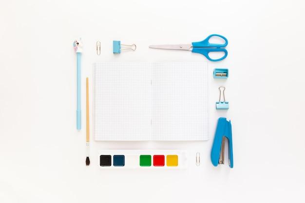 テキスト用の空きスペースの周りのテーブルに学用品と文房具を備えたモダンな白青のオフィスデスクトップの上面図。学校に戻るコンセプトフラットはモックアップで横たわっていた
