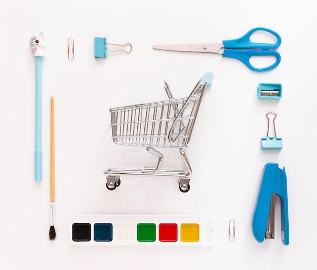 バスケットやショッピングカートとテーブルの上に学用品と文房具を備えたモダンな白青のオフィスデスクトップの上面図。学校に戻るコンセプトフラットはモックアップで横たわっていた