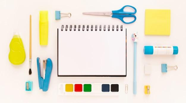텍스트를 위한 빈 공간 주위에 학교 용품과 문구류가 있는 현대적인 흰색, 파란색, 노란색 사무실 데스크탑의 상위 뷰. 학교 개념으로 돌아가기 모형이 있는 평평한 누워