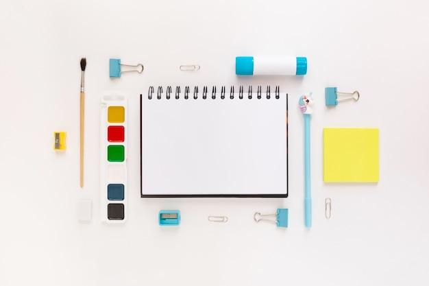 テキスト用の空きスペースの周りのテーブルに学用品と文房具を備えたモダンな白、青、黄色のオフィスデスクトップの上面図。学校に戻るコンセプトフラットはモックアップで横たわっていた