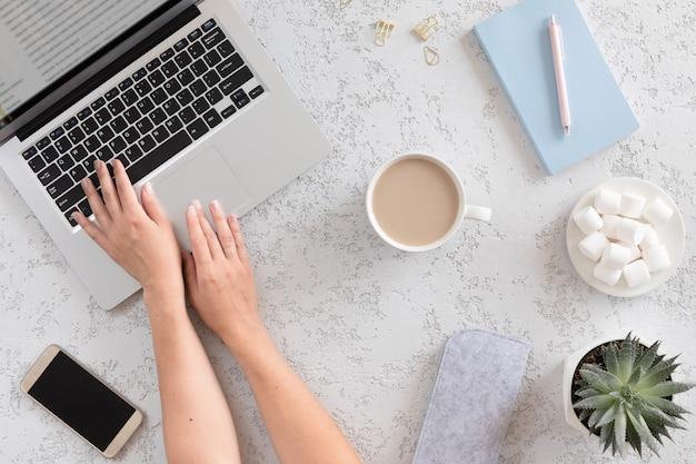 ノートパソコン、携帯電話、コーヒーカップ、ノートブック、マシュマロ、ラテコーヒーカップとモダンな白いオフィステーブルの平面図です。ミニマルなフラットレイアウト、ホームオフィスデスクワークスペース