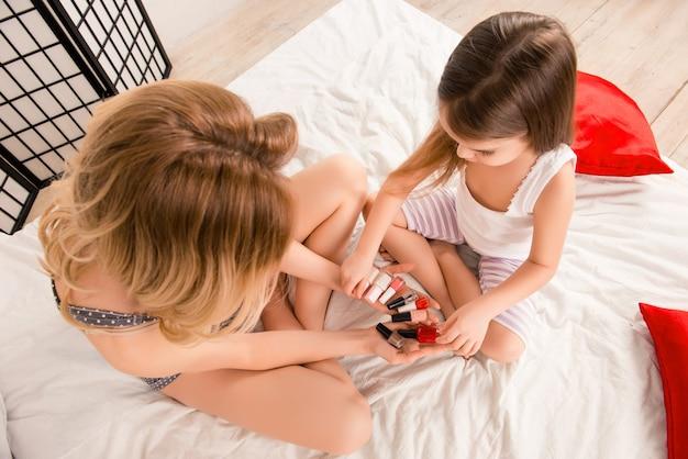 マニキュアの色を選択する母と娘の上面図