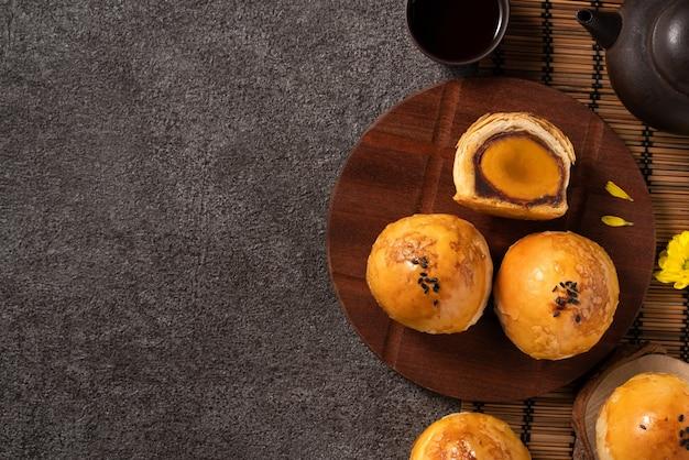 月餅卵黄ペストリー、濃い灰色のテーブルの背景に中秋節の休日の月餅の上面図