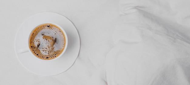 コピースペースとベッドの上の朝のコーヒーの上面図