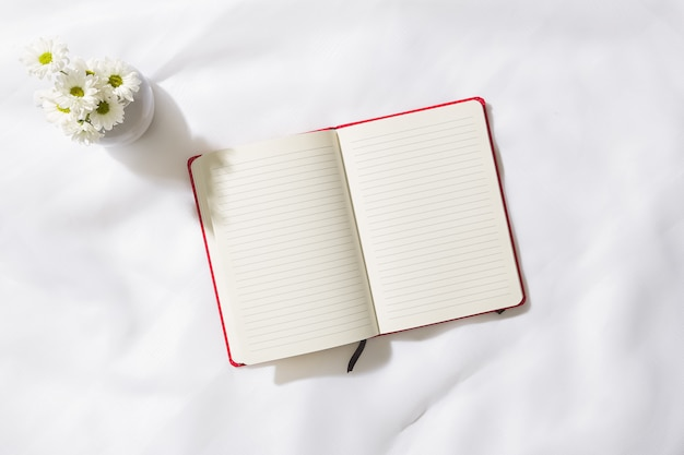 テキスト用のスペースと、真ん中に赤いノートと白い花の花瓶とボイルファブリックのバックグラウンドでの朝のシーンのトップビュー