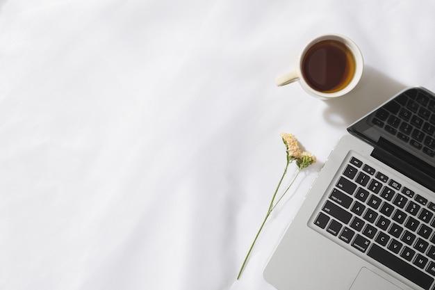 ノートパソコン、お茶のマグ、テキスト用のスペースを持つ花とボイル生地背景のモーニングティーのトップビュー