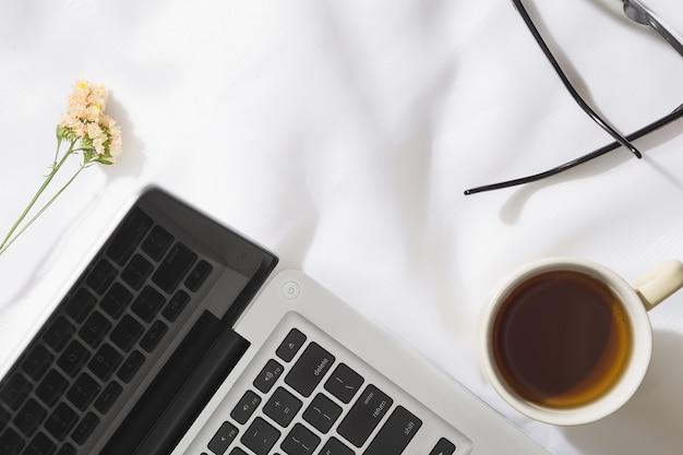 Вид сверху утреннего чая в вуаль ткани фоне с ноутбуком, кружка чая, стаканы и цветы с пространством для текста