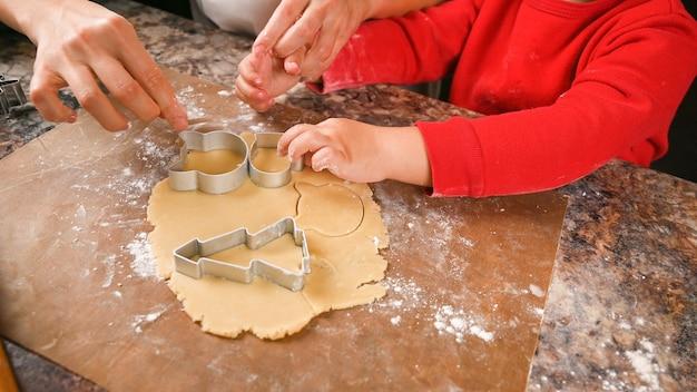 Вид сверху руки матери и ребенка, делающие рождественское печенье