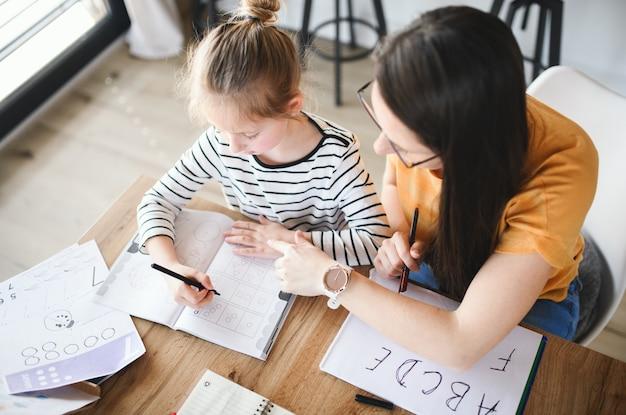 집, 코로나 바이러스 및 검역 개념에서 실내에서 학습하는 어머니와 작은 딸의 상위 뷰.