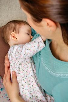 집에서 아기 딸에게 모유 수유를 하는 어머니의 상위 뷰