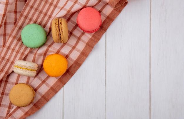 Вид сверху разноцветных макарон на коричневом клетчатом полотенце на белой поверхности