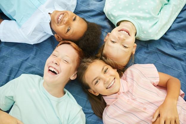 屋外の毛布の上に輪になって横たわっている子供たちの多民族グループの上面図