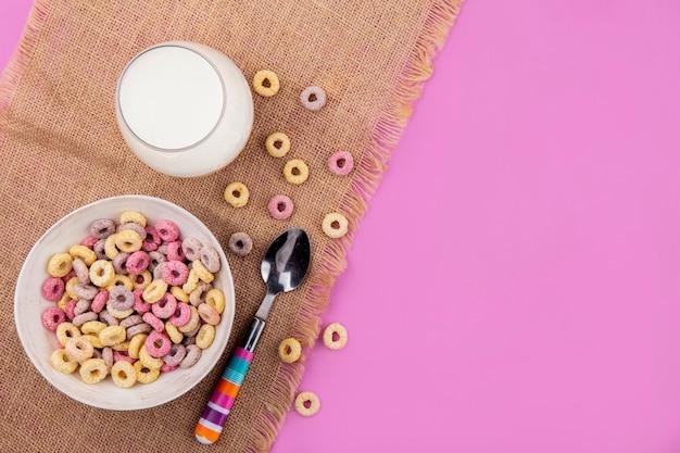 ピンクの表面に袋の布に分離された穀物とスプーンでミルクのガラスをボウルに色とりどりの穀物のトップビュー