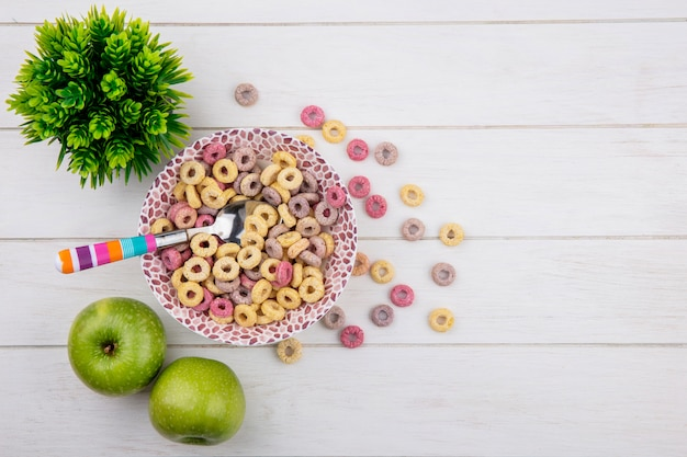 白い表面に緑のリンゴをスプーンでボウルに色とりどりの穀物のトップビュー