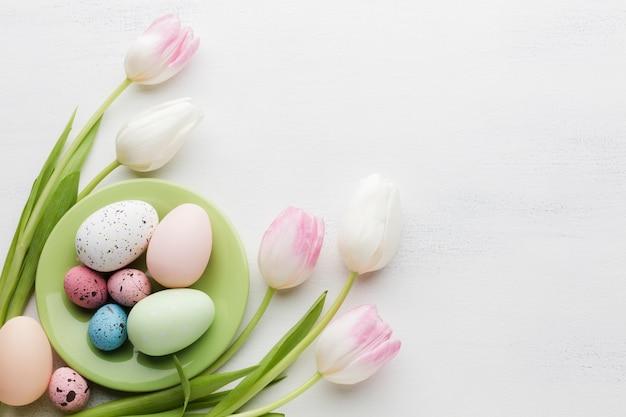튤립과 여러 가지 빛깔의 부활절 달걀의 상위 뷰