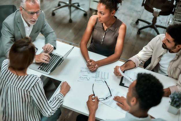 一緒にオフィスのテーブルに座ってビジネスを議論する多文化チームの上面図