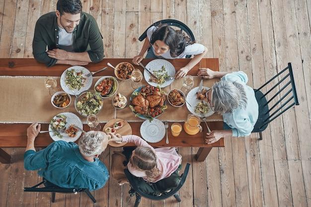 Вид сверху на многопоколенную семью, общающуюся и улыбающуюся во время совместного ужина