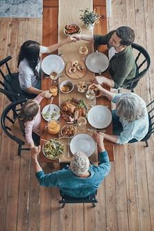 함께 저녁 식사를 하면서 손을 잡고 기도하는 다세대 가족의 상위 뷰