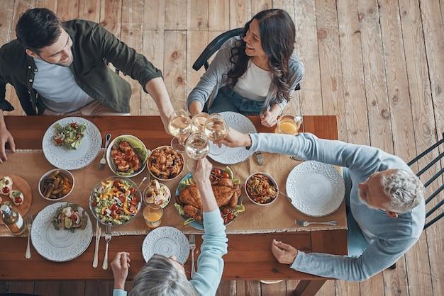 Вид сверху на тосты из разных поколений во время совместного ужина