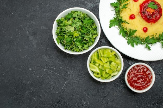 Вид сверху картофельного пюре с зеленью и томатным соусом на темноте