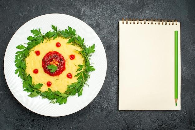 어두운 테이블에 토마토 소스와 채소와 으깬 감자 요리의 상위 뷰