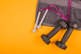 Top view of napkin with skipping rope and black dumbbells on yellow background