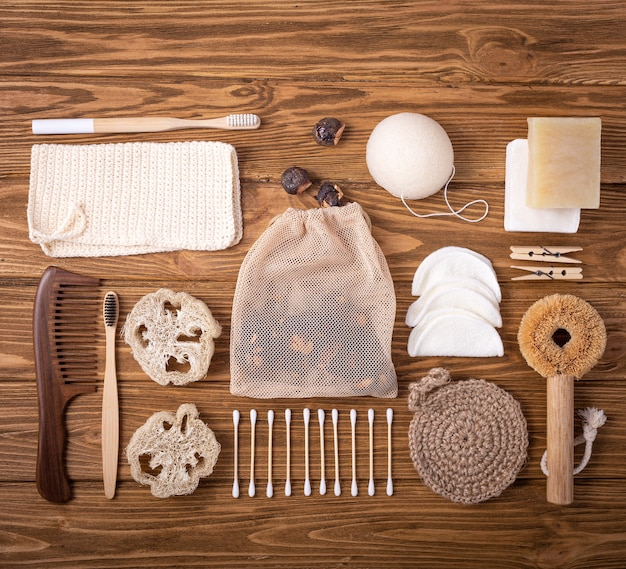 Вид сверху на натуральные кухонные и банные принадлежности, концепция жизни без отходов. набор экологически чистых аксессуаров: мыльные орехи, бамбуковая зубная щетка, щетка из сизаля, деревянные ватные палочки, люффа, губка конжак.