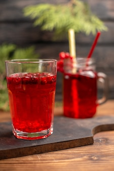 Вид сверху натурального органического свежего сока смородины в бутылке и стакане с трубками на деревянной разделочной доске