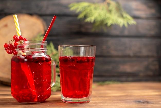 Вид сверху натурального органического свежего сока смородины в бутылке с трубками и в стакане с правой стороны на деревянном столе