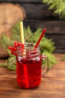 木製のテーブルにチューブを添えた瓶の中の自然な有機新鮮なカシス ジュースのトップ ビュー